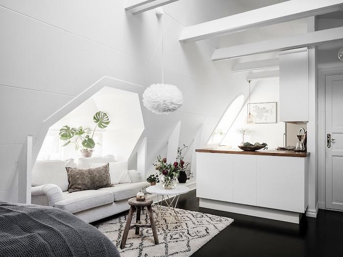 amenagement espace sous pente aux murs blancs avec ilot central avec plan de travail bois, tapis noir et blanc, poutres apparentes blanches, suspension blanche originale