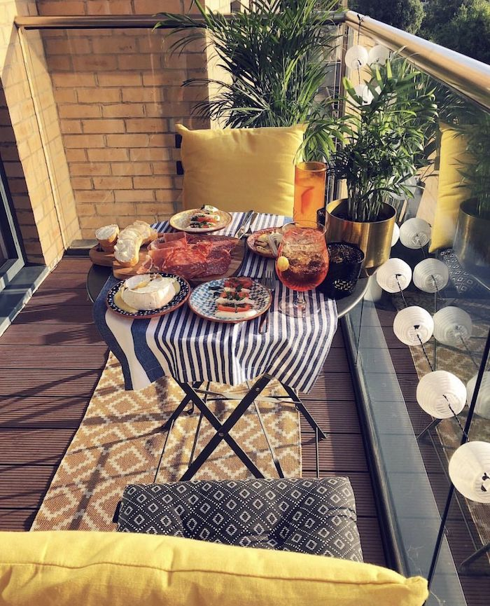 petit dejeuner servir sur le balcon, chaises rangées autour d une table ronde, tapis jaune, garde corps en verre, guirlande boule, plantes exotiques