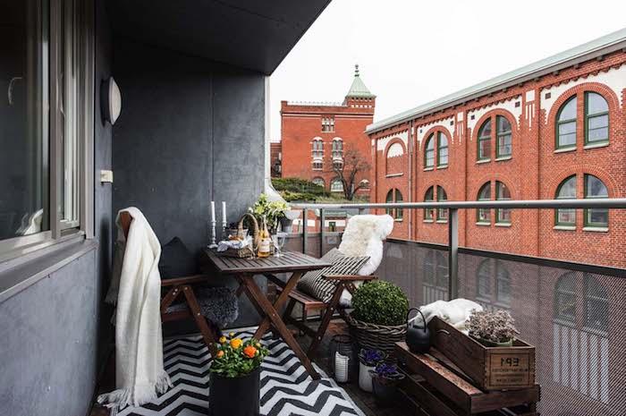 balcon avec vue sur la ville, murs gris, tapis zèbre, chaises et table bois, plantes en pots, ambiance shabby chic et cosy