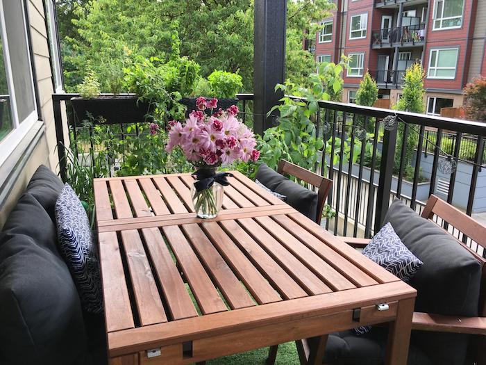 petit coin repas salle à manger exterieur composé de table bois et chaises bois décorés de coussins gris, centre de table floral