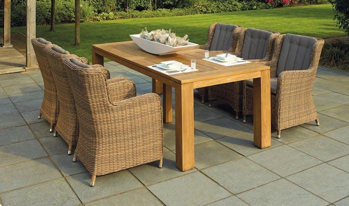fauteuils en rotin et table en bois, le parfait coin salle à manger sur une terrasse extérieure à coté d un jardin avec gazon