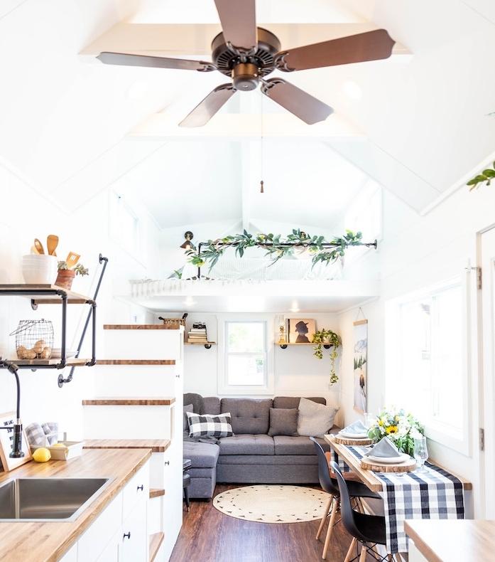canapé gris d angle dans le coin d une pièce en longueur, chambre à coucher mezzanine avec escalier, cuisine blanc et bois, coin salle à manger et parquet bois foncé