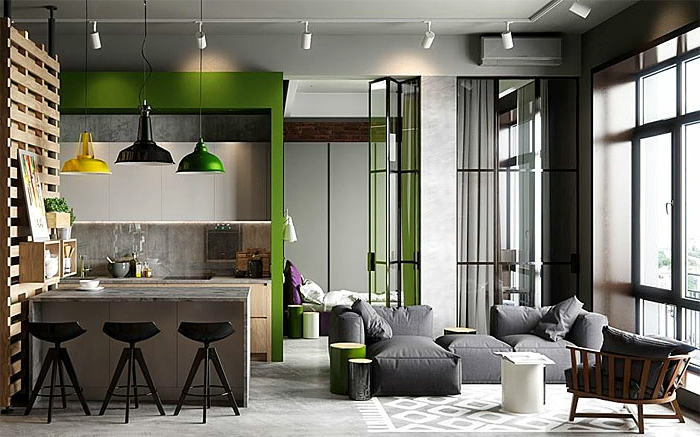 appartement gris aux accents verts, lampes pendantes suspendues, fauteuils gris, plafond en béton, coin cuisine style industriel