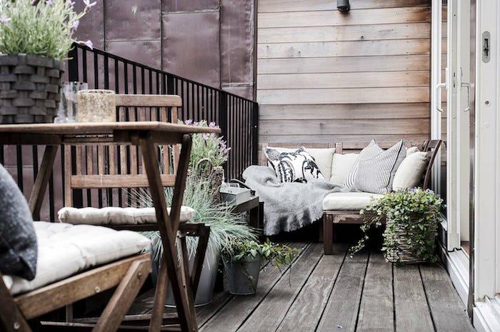 balcon en bois avec canapé d angle de bois décoré de coussins gris, chaises et table bois design, plantes en pots, garde corps noir