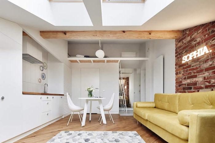 lit dessus les toilettes dans un eptit studio de 20 m2 avec cuisine blanche, table et chaises salle à manger blanches, poutre apparente bois, canapé jaune, mur de briques