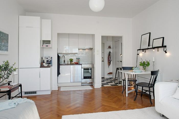 coin cuisine dans une petite niche, appartement studio scandinave, sol chevron, étagère porte cadres avec lampes ampoules, table blanhche, chaises noires
