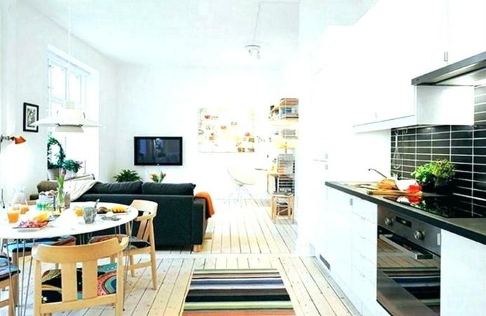 cuisine à plan ouvert, table de repas ovale, grandes chaises en bois, sofa noir, plancher en bois peint blanc, amenagement petite cuisine