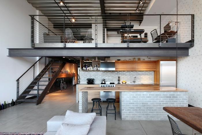mezzanine avec rambarde noire, escalier métallique, ilot en bois sur muret gris, tabourets industriels, coin travail et chambre à coucher