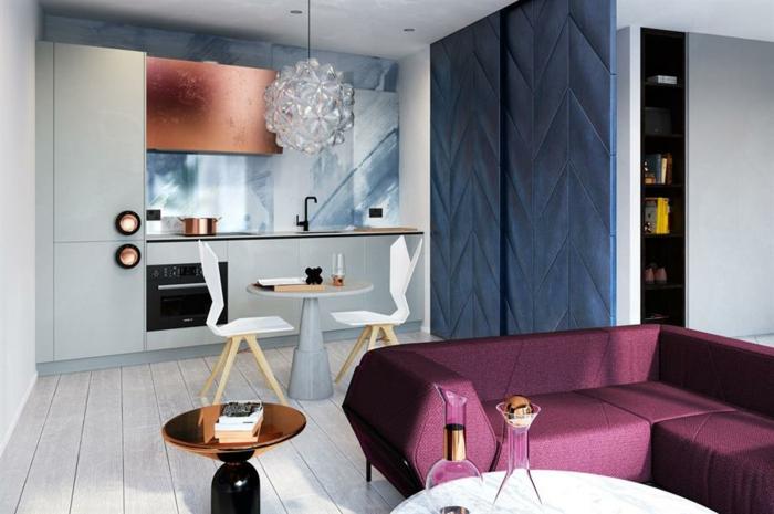 sofa pourpre, plancher blanc, lampe en cristal, petite cuisine moderne, armoire suspendue cuivrée