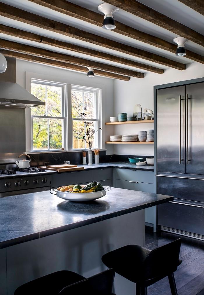 design intérieur style rustique avec poutre bois apparente, cuisine avec équipement inox et murs blancs, rangement mural étagère bois