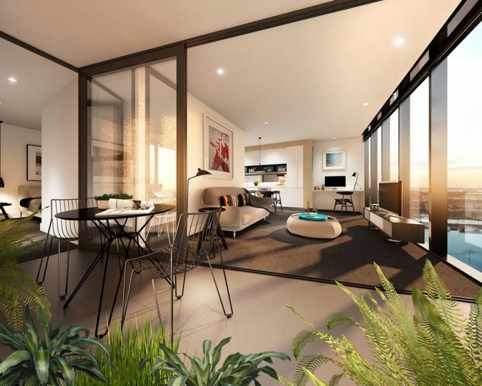 appartement studio avae petite cuisine, intérieur spacieux, mur de séparation, table ronde, chaises basket, bureau suspendu