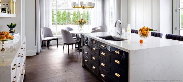 aménagement cuisine avec îlot central, exemple armoires de cuisine blanches avec poignées dorées, plan de travail marbre
