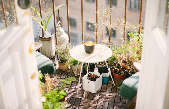 balcon fleuri avec plusieurs petits pots de fleurs posés par sol en bois, table basse blanche, garde corps en metal