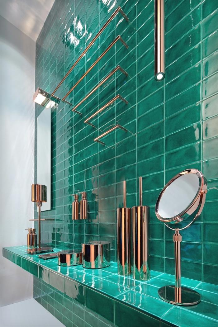 modèle salle de bain moderne aux murs blancs avec revêtement mural partiel en carreaux turquoise, objets en cuivre