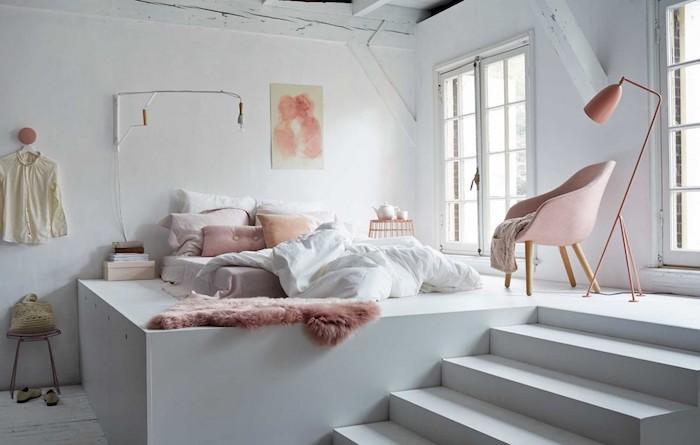 lit cocooning matelas sur estrade blanche, avec coussins et plaid rose, murs blancs, chaise fauteuil rose, ambiance hygge, deco romantique de chambre studio