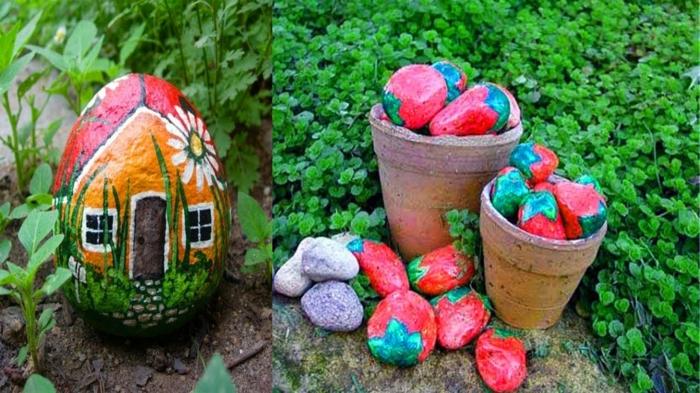 pots de fleurs remplis de galets peints comme fraises, galet dessiné maison posés dans le parterre de jardin