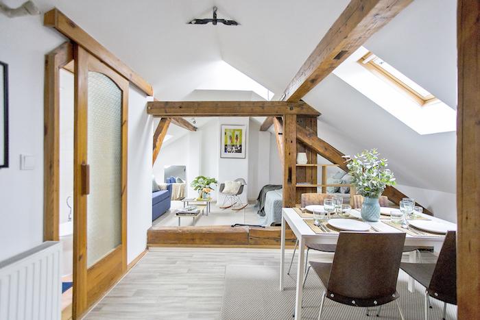 poutres apparentes dans un studio sous pente avec salle à manger ouverte sur espace salon et cahmbre à coucher, chaise à bascule, canapé bleu