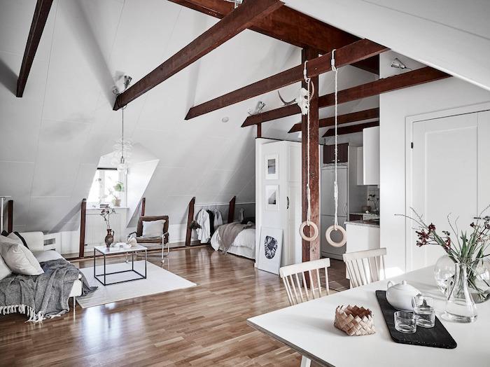 poutres apparentes dans un studio sous pente avec coin chambre sous pente, canapé blanc avec plaid gris, table minimaliste, salle à manger blanche style scandinave