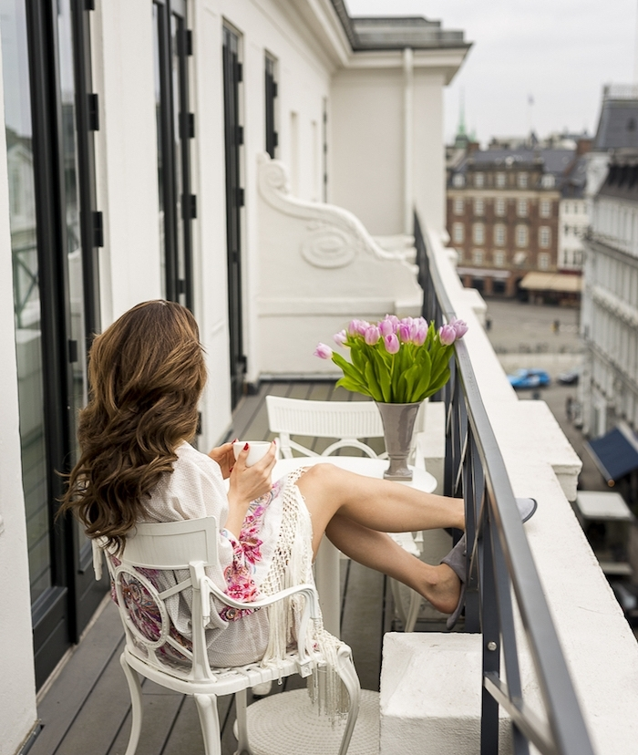 table de balcon blanche ronde et deux chaises blanches, bouquet de tulipes sur une table, revetement sol bois, femme qui prend son café sur un balcon