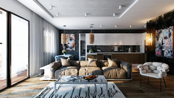 studio moderne, grand sofa moelleux trois places, plancher bois foncé, petite cuisine, grands tableaux artistiques