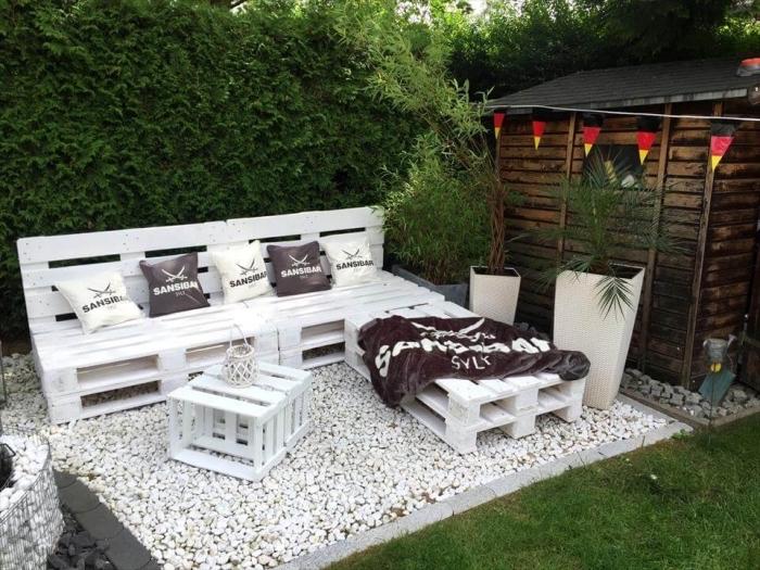 exemple de décor stylé pour une arrière-cour ou terrasse avec meubles palette repeints en blanc, accessoires décoratifs coussins et plaid en marron