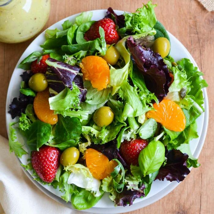salade aux roquettes et aux olives vertes, assiette blanche, clémentine, fraises, salade composée originale