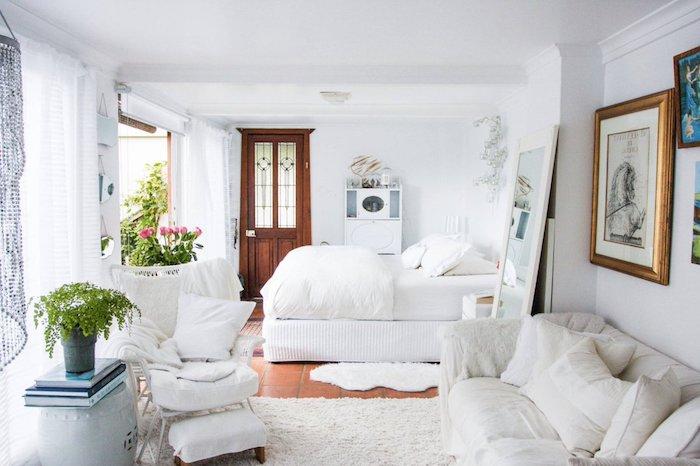 deco chabby chic feminine en blanc avec lit et canapé cocooning en blanc, deco florale, grande miroir et mur de cadres