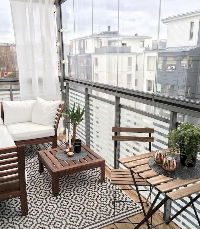 petit coin repos en canapé et table bois sur un balcon vitré avec brise vue rideau blanc, tapis gris et blanc et table et chaises bois et metal sur baclon bois