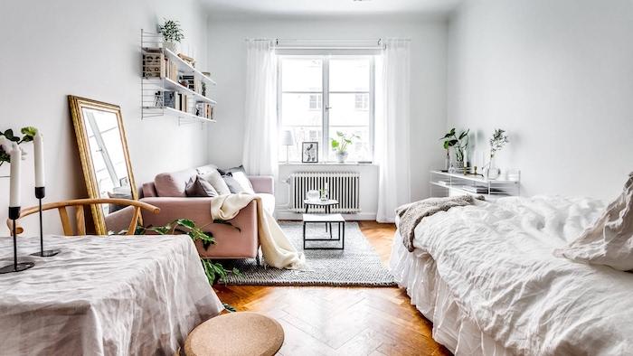 deco nordique dans une chambre à coucher design avec canapé rose, lit blanc, table simple, parquet bois,étagère pour livres