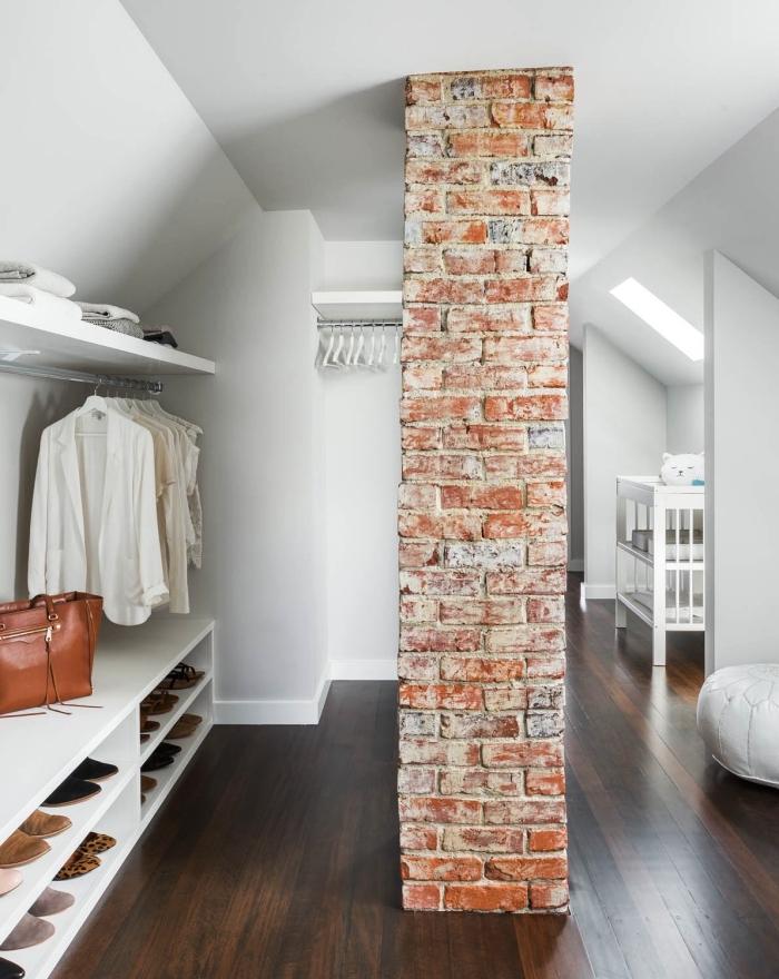 un coin dressing sous pente avec étagères ouvertes et tringles à vêtements séparé du reste de l'espace par unе colonne de briques
