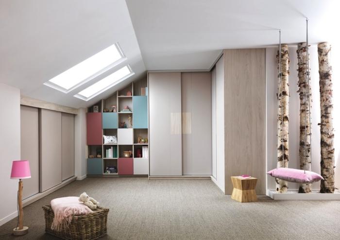 une chambre d'enfant aménagée sous les combles avec armoire sous pente à portes coulissantes et bibliothèque casier suivant la pente du toit