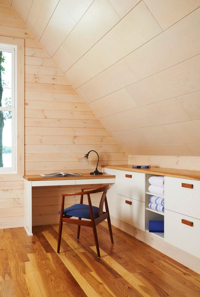 un meuble de rangement sous pente avec tiroirs, étagères et plan de travail qui fait office de coin bureau