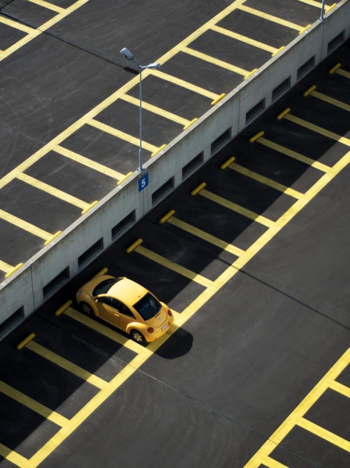une zone de stationnement avec des places de parking libres délimitées par des lignes jaunes, une voiture jaune garée sur une place de parking