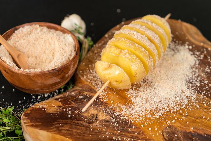 couvrir la brochette de pomme de terre de mélange de parmesan et épices, pomme de terre au four suedoise