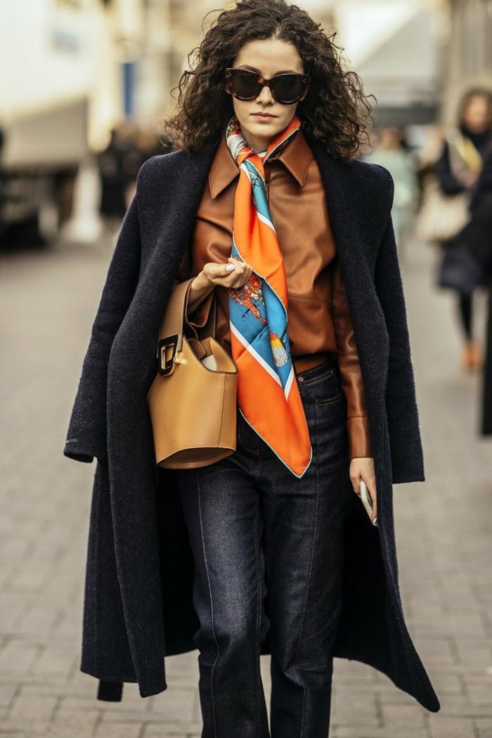 femme élégante, foulard noué à la nuque, petit sac marron, jeans bleus, chemise marron