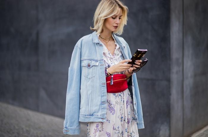 veste denim, robe blanche motifs floraux, sac rouge porté à la taille, femme blonde, sacs tendance, sac a main rouge