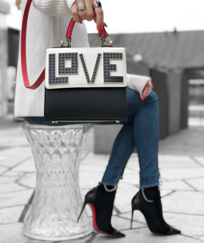 sac à main noir et blanc, sac bandoulière, jeans bleus, escarpins noirs, bandoulière rouge, sac avec inscription