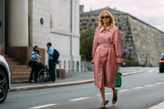 sac vert, escarpins extravagants, long manteau rose, ceinture à la taille, femme blonde dans la rue