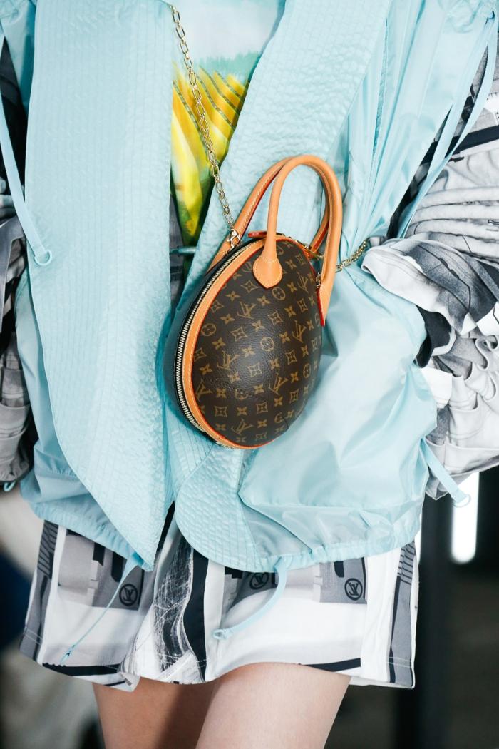 sac en forme d'oeuf, marque de sac de luxe, poignées beiges, gilet bleu, sac à main bandoulière