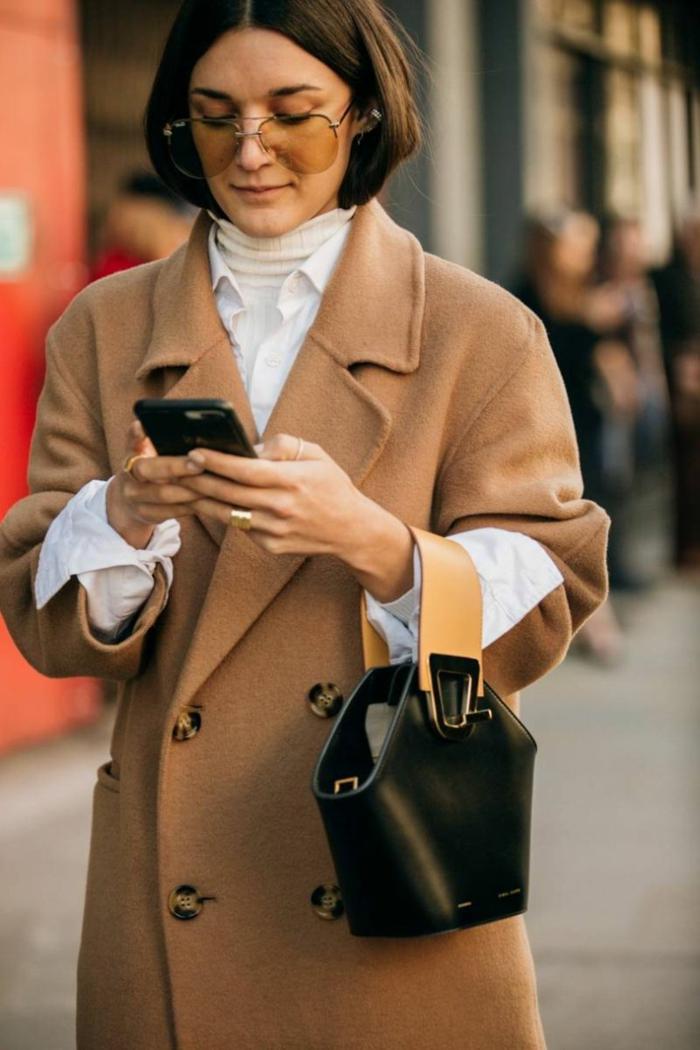 sac noir en cuir avec poignée beige, long manteau beige, pull blanc col montant, chemise blanche