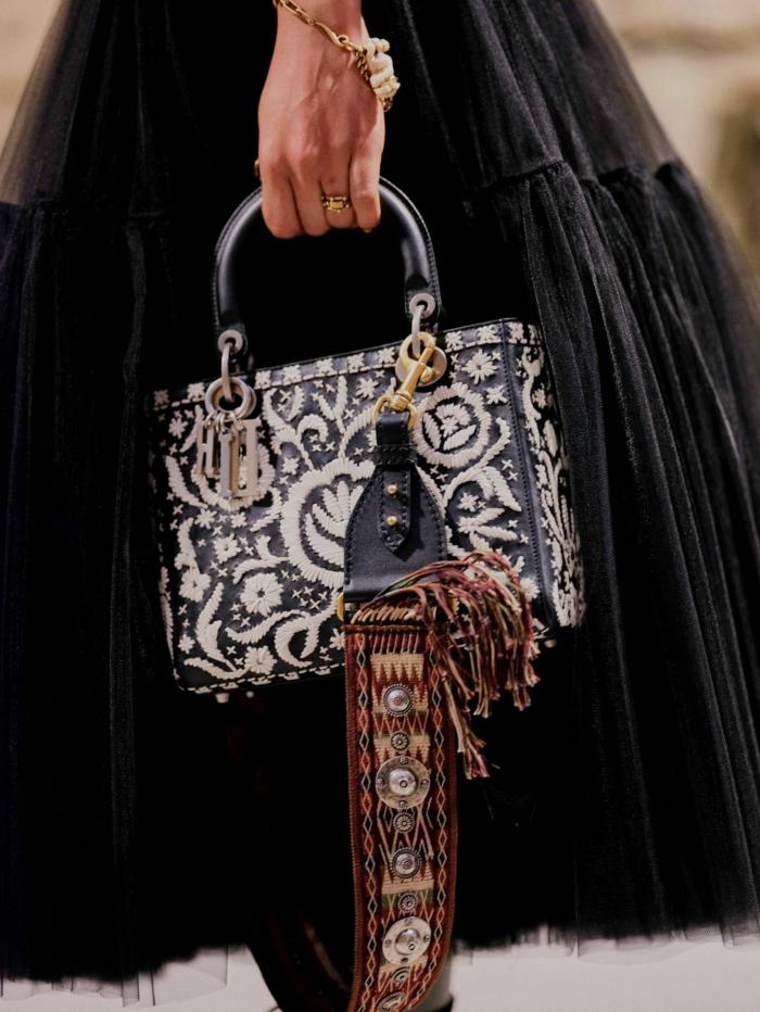 longue jupe noire, sac texturé avec figures floraux, bracelet en or, poignée statement noire