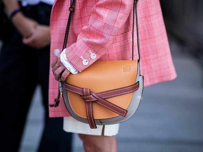 sac en marron et gris, veste rose carrrée, jupe courte blanche, sac à main original
