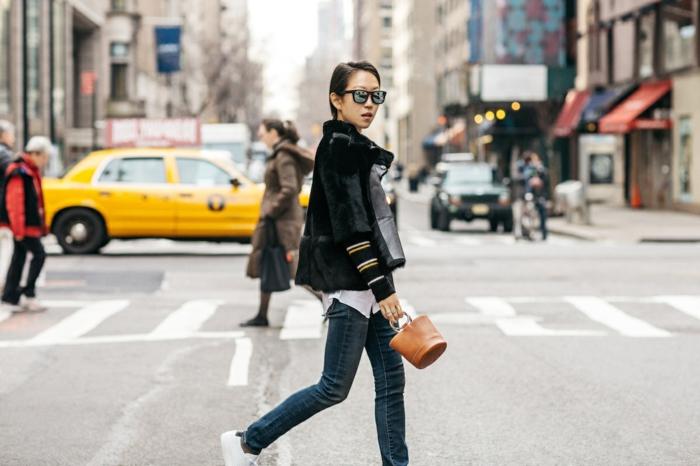 jeans bleus, sneakers blancs, petit sac en cuir marron, lunettes de soleil, veste noire en daim