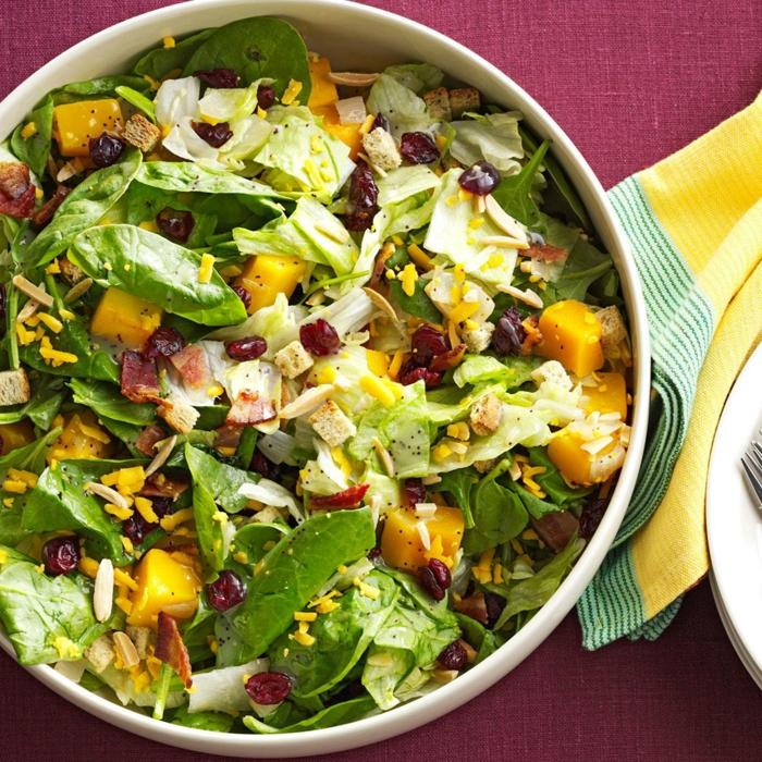 épinards, canneberges, mangue, graines de grenade, bol blanc, serviette jaune, nappe rouge