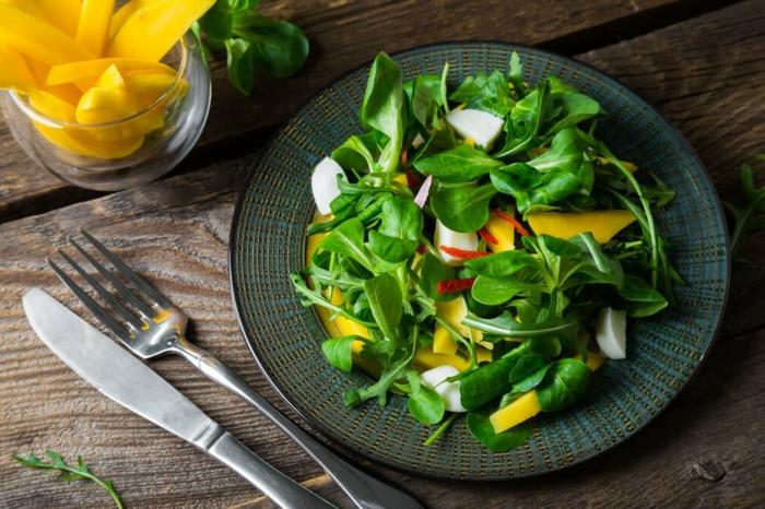 légumes et fruits mixés en salade verte, mangue, assiette noire, tasse pleine de morceaux de mangue