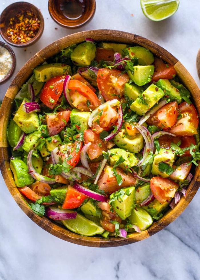 salade avocat, tomates, oignon, avocat en tranches, grand bol en bois, salade légère apétissante