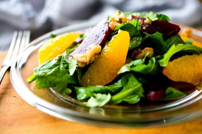 salade d'hiver aux betteraves, oranges, épinards, assiette en verre, noix de noyer