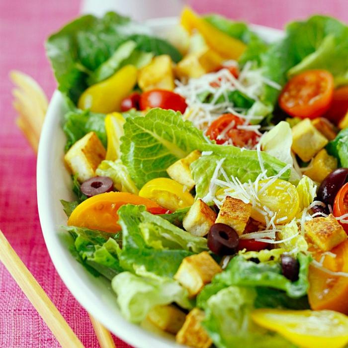salade cesar, croutons de tofu, olives hachées, tomates cerises rouges et jaunes, fromage râpé