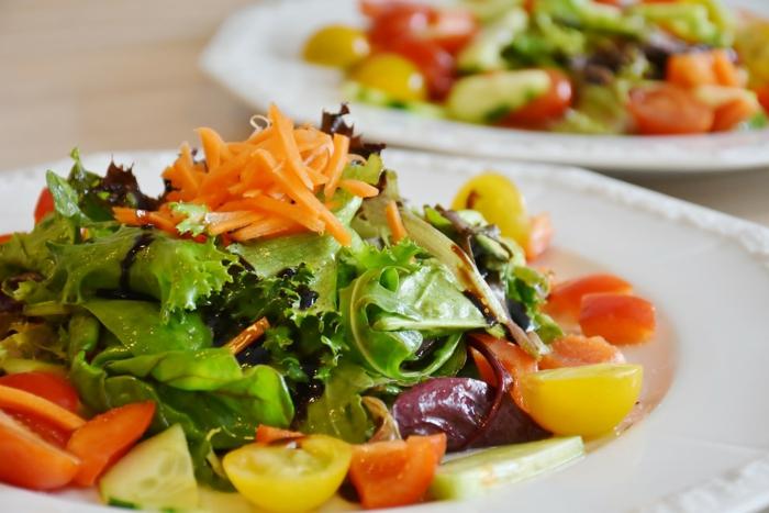 salade laitue, carottes, tomates cerises jaunes et rouges, concombres, assiettes de salade
