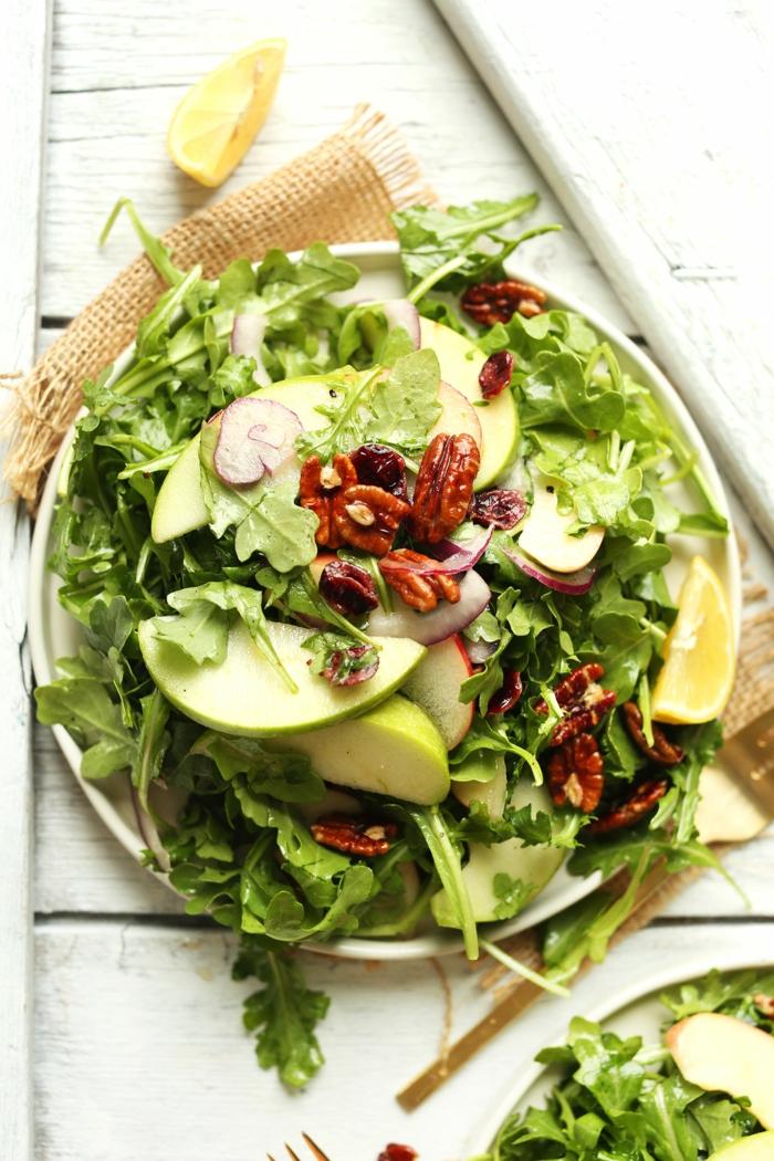 assiette blanche, pommes vertes, noix de pécans, roquette, planches peintes blanches